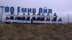 Workers at Emir Oil, Kazakhstan, display a banner protesting at the legal attack on independent trade unions. Photo by KNPRK.