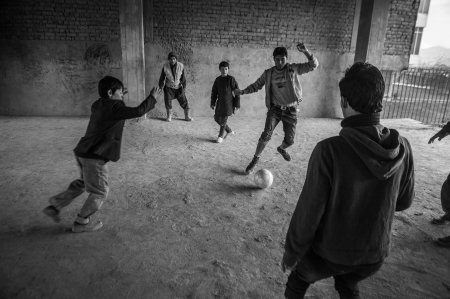 Boys at the Chamn-e-Babrak camp playing football in the car park of a semi-completed but long abandoned housing development (2014). By Guy Smallman.