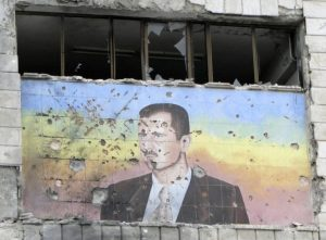 A picture of Bashar al-Assad riddled with holes on the facade of the police academy in Aleppo, after it was captured by Free Syrian Army fighters, March 4, 2013. Photo Reuters/Mahmoud Hassano)
